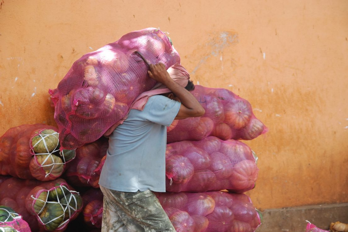 man carrying sack of melons